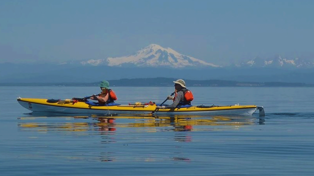 Side view of two people in a yellow kayak with mountain peak in background