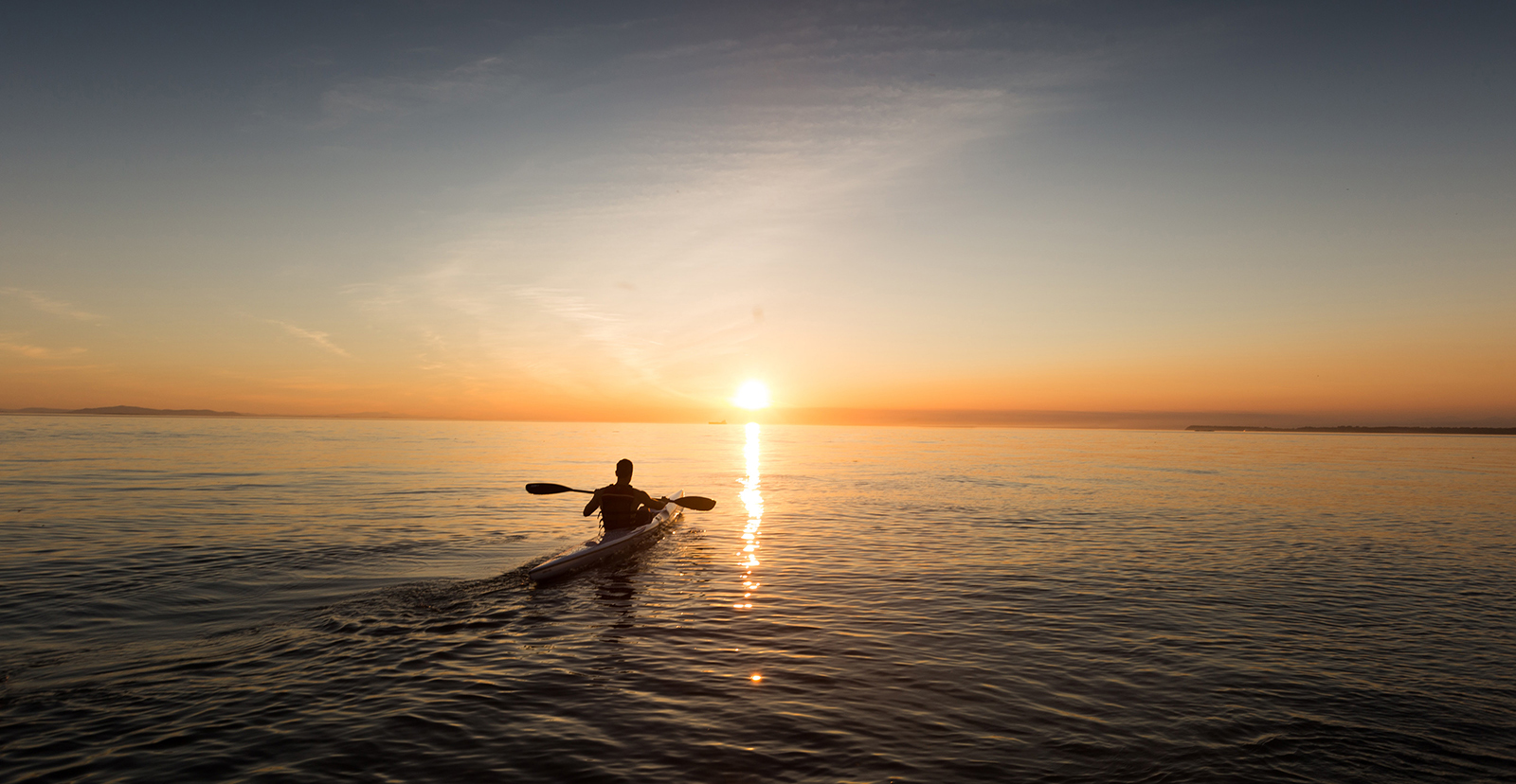 Silhouette of person in kayak padding towards sunset over water