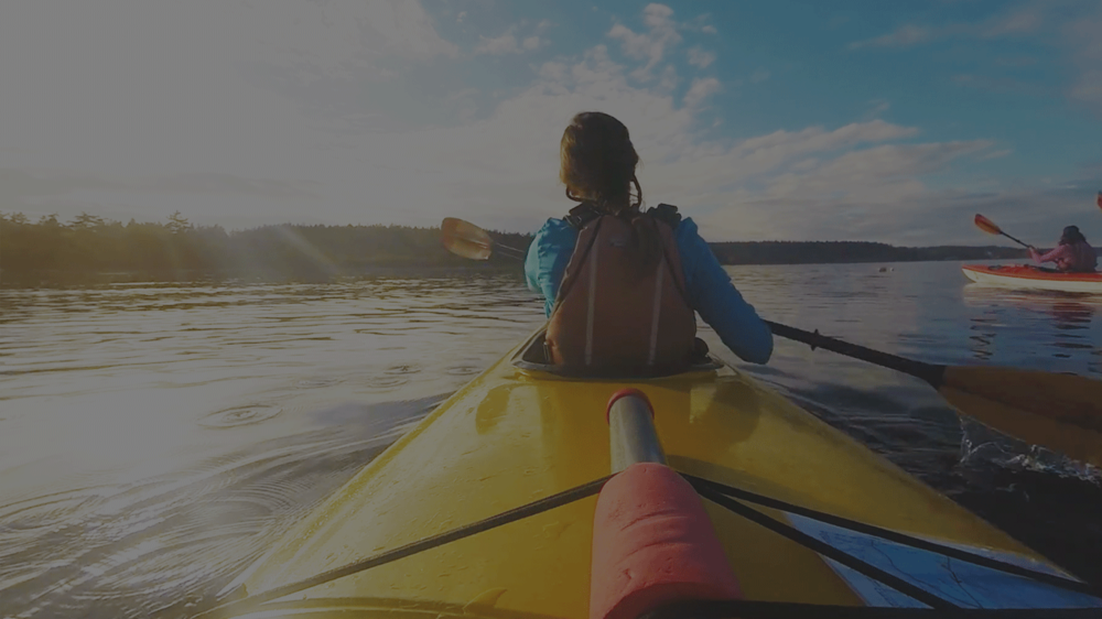 View from the back of person sitting in front of yellow kayak on water
