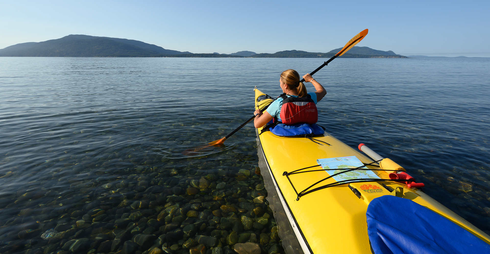 three-quarter view of yellow kayak in lower right corner with person paddling in front